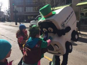 Two men and a truck's mascot Truckie says hello to kids at a parade
