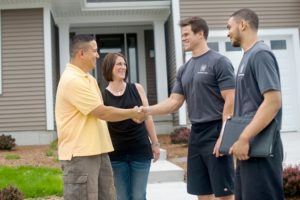 TWO MEN AND A TRUCK professional movers shake hands with happy customers