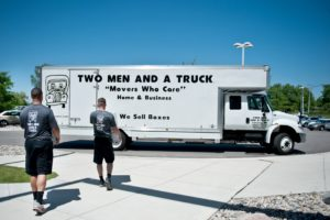 TWO MEN AND A TRUCK professional movers walk toward their truck