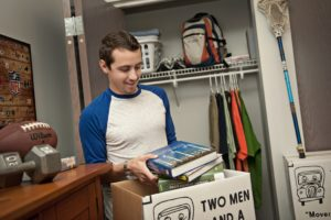 A college studentss unpacks TWO MEN AND A TRUCK moving boxes in his dorm room