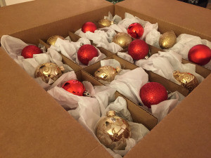 TWO MEN AND A TRUCK carefully packs ornaments into a dish pack box
